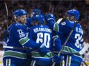 The Vancouver Canucks, including Daniel Sedin, left, and and Henrik Sedin, right, celebrate Markus Granlund's second goal against the San Jose Sharks during Friday's game at Rogers Arena.