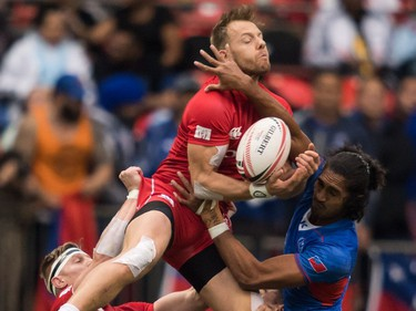 Canada's Harry Jones, top, is lifted by John Moonlight, left, as he vies for the ball against Samoa's Silao Nonu, right, during World Rugby Sevens Series action, in Vancouver, B.C., on Sunday March 11, 2018.