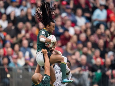 South Africa's Cecil Afrika, top, is lifted by Zain Davids, left, as he grabs the ball away from Fiji's Sevuloni Mocenacagi, back, during World Rugby Sevens Series action, in Vancouver, B.C., on Sunday March 11, 2018.