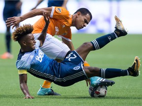 Vancouver Whitecaps' Yordy Reyna, front, is upended by Houston Dynamo's Juan David Cabezas during the first half of an MLS soccer game in Vancouver, B.C., on Saturday August 19, 2017.