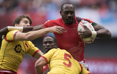 Daniel Sikuta of Kenya is chased by Pablo Fontes (left) and Manuel Sainz of Spain during the World Rugby Seven Series at B.C. Place in Vancouver, Saturday, March 10, 2018.