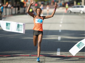 Monicah Ngige is the first female runner to cross the finish line at The Vancouver Sun Run on April 22.