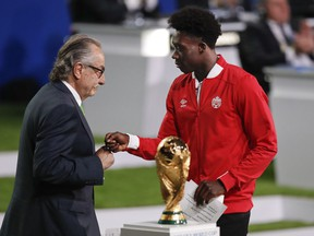 Decio de Maria, President of the Football Association of Mexico, left, and Canadian soccer player Alphonso Davies, right, present a joint United bid by Canada, Mexico and the United States to host the 2026 World Cup at the FIFA congress in Moscow on June 13.