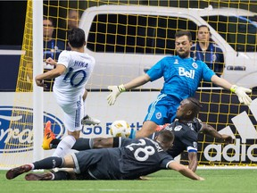 San Jose Earthquakes' Jahmir Hyka (10) is stopped by Vancouver Whitecaps goalkeeper Stefan Marinovic, back right, as Kendall Waston and Jake Nerwinski (28) defend during the second half of an MLS soccer game in Vancouver, on Saturday September 1, 2018.