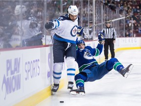 Winnipeg Jets' Dustin Byfuglien fights off Vancouver Canucks' Tim Schaller during the first period on Monday night.