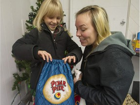 Tasha Nickles and her daughter Aria, 7, at the Surrey Christmas Bureau with items donated from The Province Empty Stocking Fund.