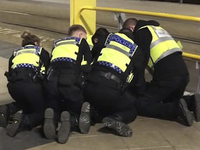 Police restrain a man after he stabbed three people at Victoria Station in Manchester, England, late Monday Dec. 31, 2018. (Sam Clack/PA via AP)