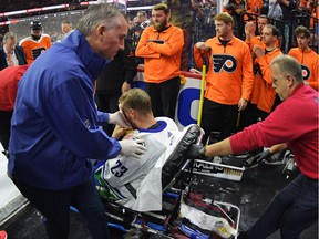 Alex Edler is helped off the ice after suffering a third-period injury Monday.