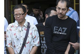 Khamla Wong, a Laos-born Canadian drug suspect, right, and his Chinese accomplice, Fangyong Saeyang, are escorted by police in Bangkok in 2016. Wong was later mysteriously released.