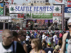 People walk past the main stage at the first day of Hempfest, Friday, Aug. 16, 2013, in Seattle. They both came from humble beginnings: small protests against marijuana prohibition where activists smoked weed in public, boldly defying what they considered an unjust law. But as Vancouver's 4-20 and Seattle's Hempfest grew into large-scale occasions with vendors, prominent musical acts and tens of thousands of attendees, the Canadian event has drawn scorn and opposition from elected officials, while American politicians have tolerated and even supported the gathering.