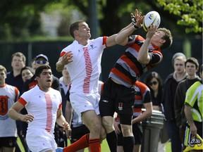 St. George's Saints, in white, complete hard against Lord Byng at the B.C. boys sevens rugby championship final at UBC's Wolfson Field on April 27, 2014.
