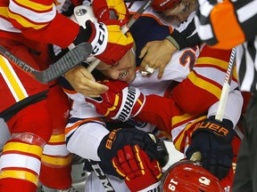 Edmonton Oilers Milan Lucic is tangled up with Calgary Flames in NHL hockey action at the Scotiabank Saddledome in Calgary, Alta. on Saturday November 17, 2018.