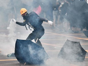 A protester throws back a round of tear gas fired at protesters by the police during a demonstration in the district of Yuen Long in Hong Kong on July 27, 2019.