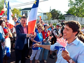 Prime Minister Justin Trudeau points to Conservative Leader Andrew Scheer while walking with the crowd during the Tintamarre in celebration of the National Acadian Day and World Acadian Congress in Dieppe, N.B., on Aug. 15.