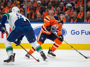 Connor McDavid of the Edmonton Oilers skates the puck past Tyler Myers of the Vancouver Canucks during the second period at Rogers Place.