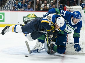 Vancouver Canucks blueliner Alex Edler (right) hauls down St. Louis Blues centre RyanO'Reilly in what was an intensely physical NHL game at Rogers Arena on Nov. 5, 2019.