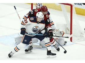 Edmonton Oilers center Ryan Nugent-Hopkins (93) and Arizona Coyotes left wing Lawson Crouse (67) try to get a stick on the puck during the third period of an NHL hockey game Wednesday, Jan. 2, 2019, in Glendale, Ariz. The Oilers defeated the Coyotes 3-1.
