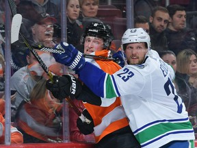 Alex Edler, right, couldn't or wouldn't say when he'll return to the Canucks' roster, but the Vancouver veteran has been missed. Coach Travis Green didn't rule out a return before Christmas.