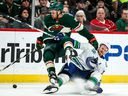 Minnesota Wild forward Jordan Greenway hits Vancouver Canucks defenceman Alexander Edler during the first period at Xcel Energy Center.