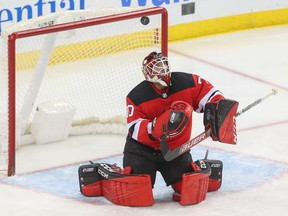 Louis Domingue looks for the puck after making a stop for the Devils on Feb. 11.
