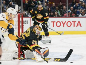 Vancouver Canucks goalie Jacob Markstrom (25) makes a save on Nashville Predators forward Nick Bonino (13) during the second period  in a game at Rogers Arena.