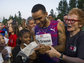Canadian sprint star Andre De Grasse signs autographs after running the men's 100-metre race at the 2017 Vancouver Sun Harry Jerome Track Classic.