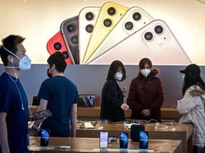 Apple staff and customers, wearing facemasks to protect against the COVID-19 coronavirus, are seen on the shop premises in Beijing on Feb. 22, 2020.