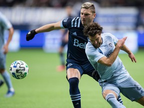 Vancouver Whitecaps' David Milinkovic, back left, and Sporting Kansas City's Graham Zusi vie for the ball during the first half of an MLS soccer game in Vancouver Feb. 29, 2020.