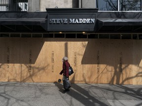 Vancouver police have arrested 40 suspects in connection to commercial break and enters at shops shuttered by COVID-19. A woman wearing a mask walks past Steve Madden on Robson Street that has been boarded up during the COVID-19 virus in Vancouver, BC, April, 6, 2020.