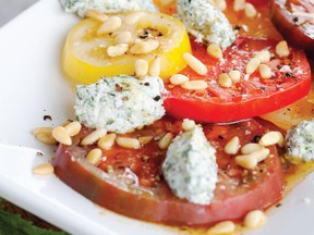Sliced heirloom tomatoes are crowned by a sprinkling of pine nuts and dollops of herbed ricotta. Photo: Janis Nicolay
