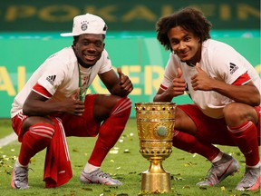 Bayern Munich's Canadian midfielder Alphonso Davies, left, and Bayern Munich's Dutch forward Joshua Zirkzee celebrate with the German Cup (DFB Pokal) trophy after winning the final match against Bayer 04 Leverkusen at the Olympic Stadium in Berlin on July 4, 2020.