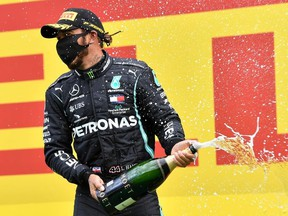 Mercedes' Lewis Hamilton wears a protective face mask as he celebrates winning the race on the podium, following the resumption of F1 after the outbreak of the coronavirus disease (COVID-19).