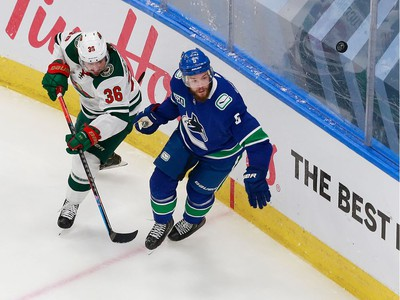 Oscar Fantenberg #5 of the Vancouver Canucks and Mats Zuccarello #36 of the Minnesota Wild pursue the puck in Game 2.