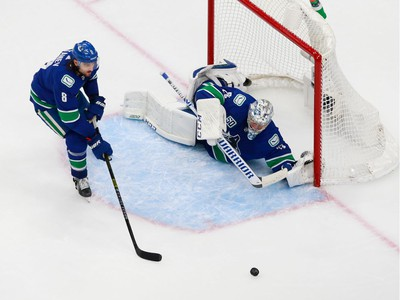 Jacob Markstrom #25 and Chris Tanev #8 defend the net in Game 2.