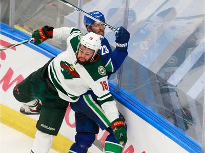 Jordan Greenway #18 of the Minnesota Wild checks Alexander Edler #23 of the Vancouver Canucks in Game 2.