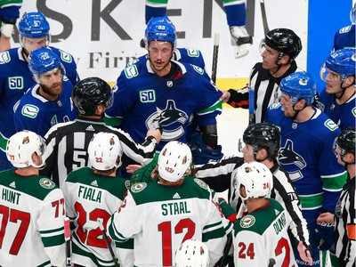 Jay Beagle #83 of the Vancouver Canucks exchanges words with Eric Staal #12 of the Minnesota Wild at the end of Game 2.