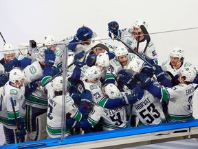 The Vancouver Canucks celebrate their Game 2 overtime victory on Friday against the St. Louis Blues at Rogers Place in Edmonton. The Canucks won 4-3 to grab a 2-0 lead in the best-of-seven series. Game 3 is Sunday.