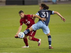Vancouver Whitecaps midfielder Russell Teibert (31) battles for the ball with Toronto FC forward Pablo Piatti at BMO Field on Aug. 21.