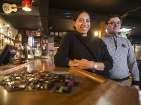 Natalya Mason, right, education coordinator for Saskatoon Sexual Health, and Damian Andersen-Crouch, volunteer with Saskatoon Sexual Health, with some samples of condoms and drink coasters distributed to local bars during the organization's Condom Blitz at the Capitol bar in Saskatoon on Nov. 28, 2019.
