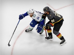 Tyler Motte of the Vancouver Canucks, left, battles for puck possession with Paul Stastny of the Vegas Golden Knights during the Stanley Cup playoffs at Rogers Place in Edmonton earlier this month.