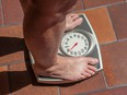 Overweight person weighing herself on a bathroom scale.
