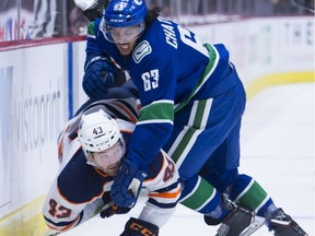 Canucks defenceman Jalen Chatfield puts Edmonton Oilers right-winger Josh Currie into the boards during pre-season action in Vancouver last year.