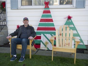 Retired carpenter Bill Day sits in one of the Adirondack chairs he made in his home shop as part of an Empty Stocking Fund fundraiser at Rogers Sugar.