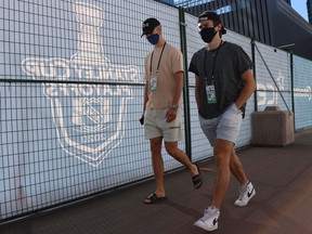 Elias Pettersson (left) and Quinn Hughes of the Vancouver Canucks walk at Rogers Place on July 29, 2020 in Edmonton. Players from Europe and the U.S. will have to quarantine in Vancouver for 14 days before training camp opens on Jan. 3.
