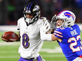 Baltimore Ravens quarterback Lamar Jackson (8) stiff arms Buffalo Bills strong safety Micah Hyde (23) during the AFC Divisional Round playoff game in Buffalo.