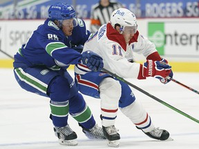 Vancouver Canucks defenceman Nate Schmidt (88) fights for control of the puck with Montreal Canadiens right wing Brendan Gallagher (11) during first period NHL action in Vancouver, Thursday, January 21, 2021.