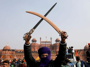 A farmer holds up a sword during a protest against farm laws introduced by the government, at the historic Red Fort in Delhi, India, Tuesday, Jan. 26, 2021.