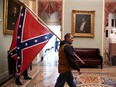 A supporter of President Donald Trump carries a Confederate battle on the second floor of the U.S. Capitol near the entrance to the Senate after breaching security defences, in Washington, U.S., January 6, 2021.