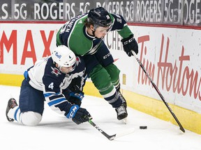 Vancouver Canucks forward Jake Virtanen battles with Winnipeg Jets defenceman Neal Pionk in the second period at Rogers Arena Friday night.