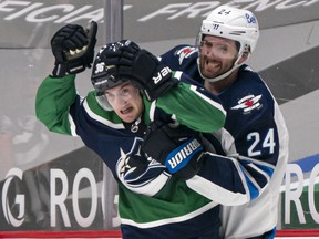 Nils Hoglander of the Vancouver Canucks reacts after getting grabbed by Derek Forbort of the Winnipeg Jets during NHL hockey action at Rogers Arena on Friday.